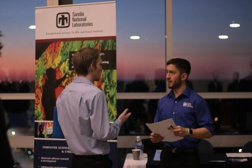 A representative from Sandia National Laboratories  interviews a student